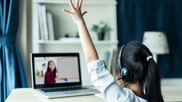 girl at laptop with hand raised