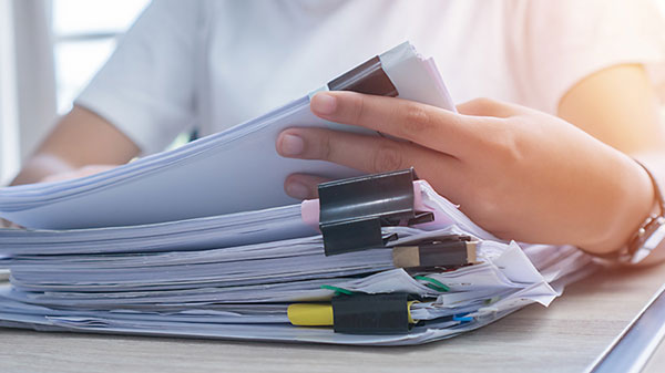woman working on a stack of reports
