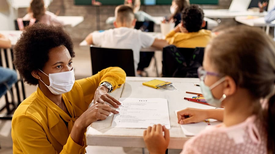 Teacher and students in classroom wearing masks.